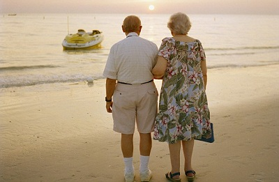 Senior couple on beach, rear view